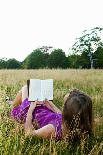 Молодая женщина читает книгу в поле — стоковое фото