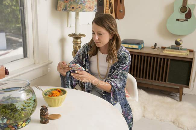 Mujer sentada en la mesa del comedor y mirando el teléfono inteligente - foto de stock