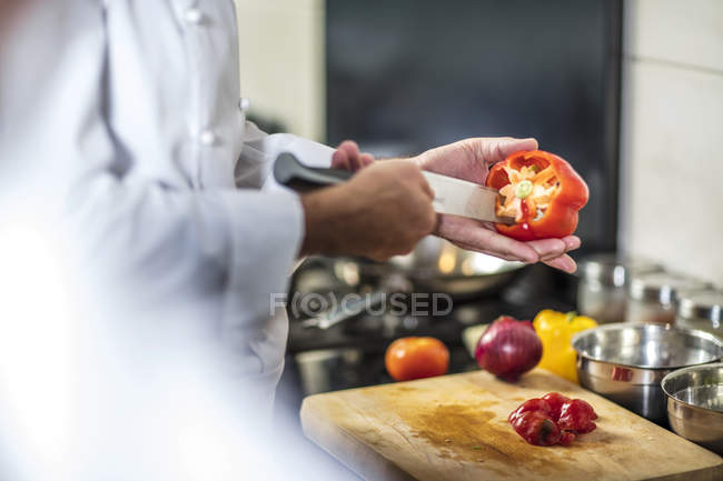 Chef de-seeding red pepper with knife — Stock Photo