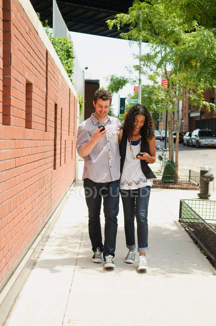 Couple walking down street, looking at cellphones — Stock Photo