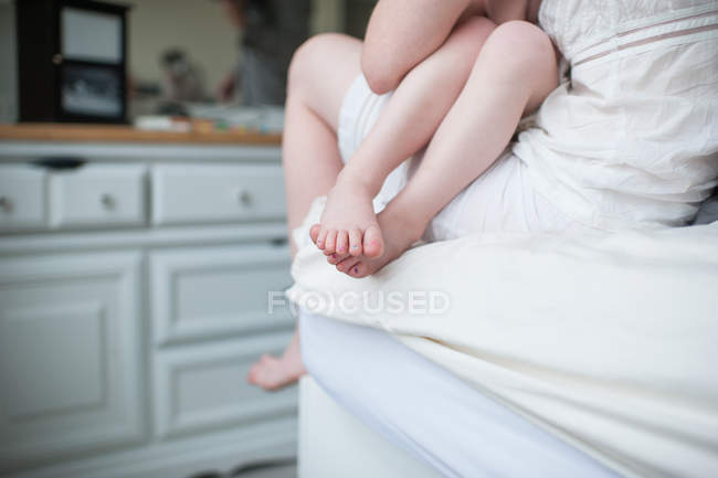 Daughter sitting on mother knee, cropped composition of bare legs and feet — Stock Photo