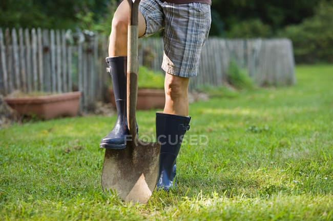 Садовник в резиновых сапогах с помощью лопаты на газоне — стоковое фото