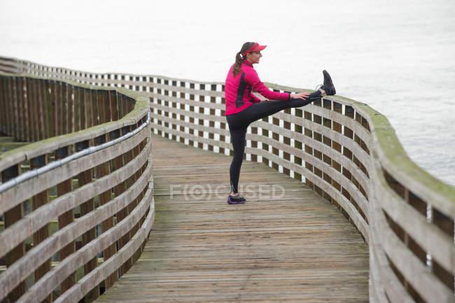 Бегун растягивается на деревянном причале — стоковое фото