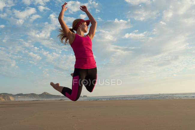 Young woman jumping in the air on beach — Stock Photo
