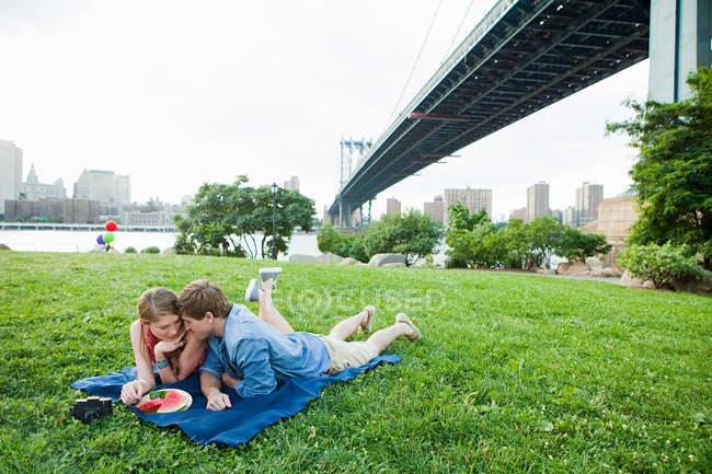 Молода пара, маючи пікнік у парку — стокове фото