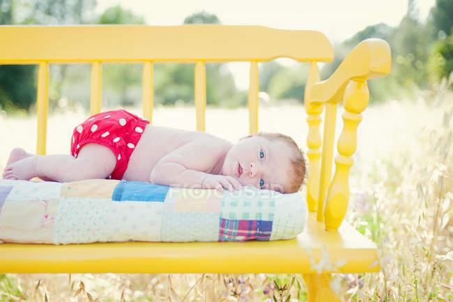 Новонароджених baby girl лежачи на жовтий лавці в галузі — стокове фото
