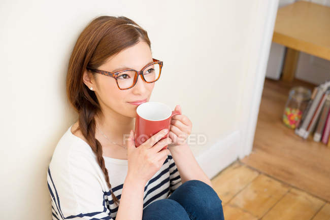 Woman day dreaming with mug of drink — Stock Photo