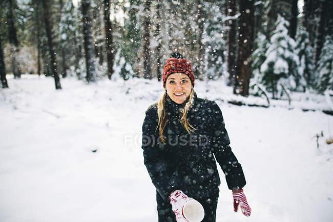 Женщина в заснеженном лесу выбрасывает снег из чашки — стоковое фото