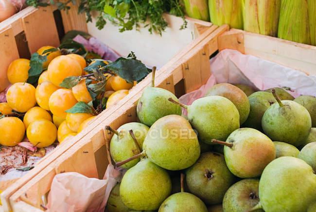 Peras e ameixas na barraca de frutas — Fotografia de Stock