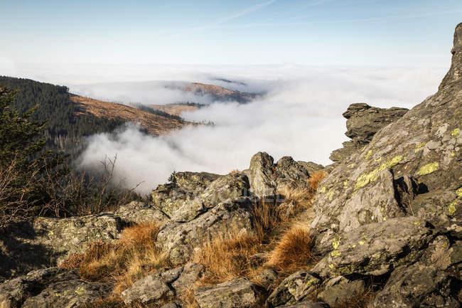 Nuages bas et le sommet de la montagne rocheuse en plein soleil — Photo de stock