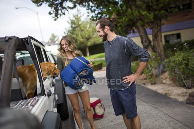 Jovem casal e cão, preparando-se para carregar o jipe para viagem — Fotografia de Stock