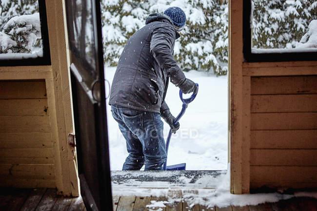 Hombre paleando nieve del camino, vista trasera - foto de stock