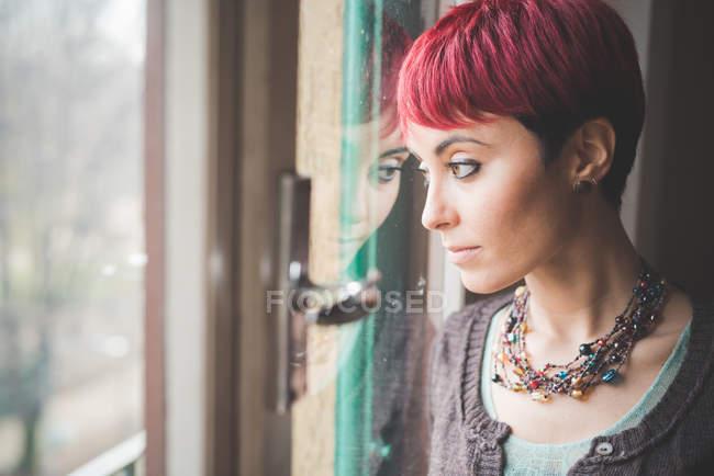 Giovane donna che osserva dalla finestra, espressione pensierosa — Foto stock