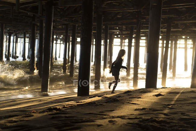 Silhouette of girl running from lapping waves underneath Santa Monica pier, California, USA — Stock Photo