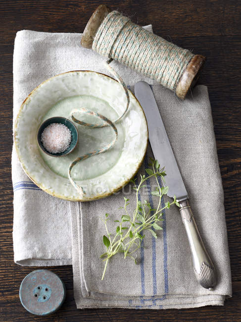 Saucer, string, knife and herbs on kitchen towel — Stock Photo