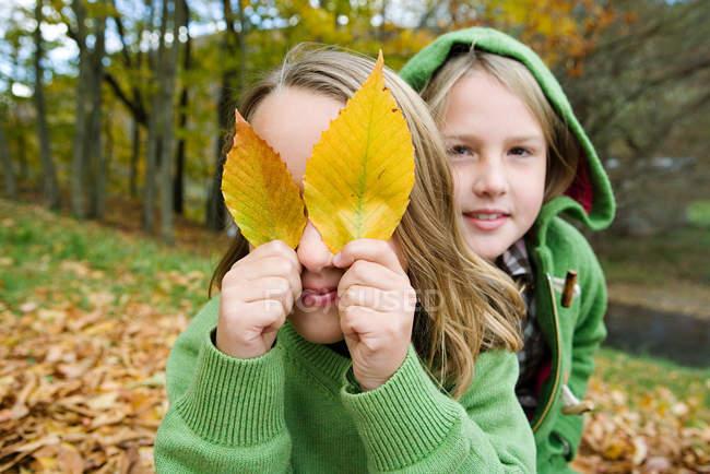 Filles jouant avec des feuilles à l'extérieur — Photo de stock