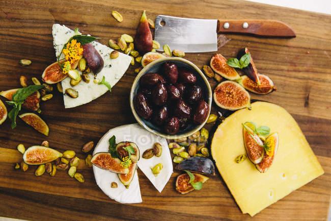 Cabezas de queso con higos en mesa - foto de stock