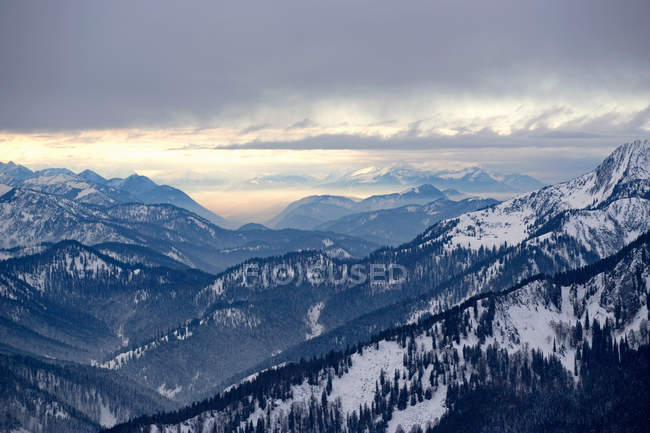Snowcapped alpine mountains with cloudy sunset sky — Stock Photo