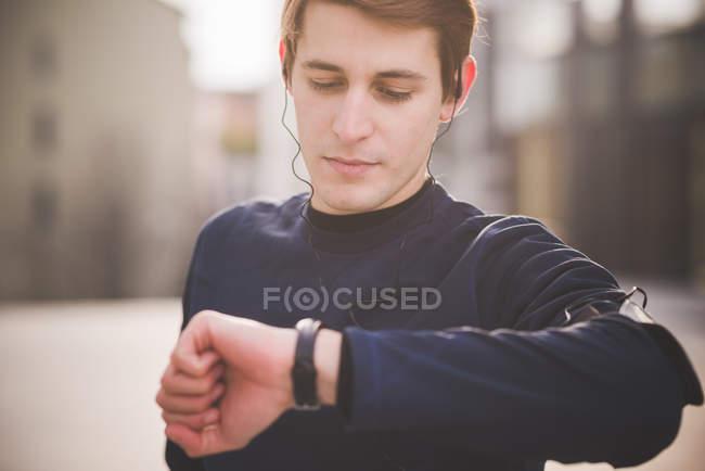 Молодой бегун проверяет наручные часы на городской площади — стоковое фото