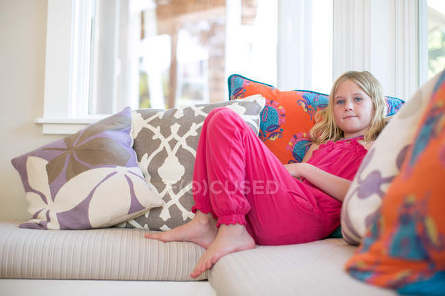 Portrait of girl reclining on sofa — Stockfoto
