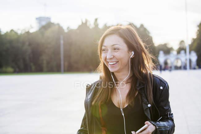 Mid adult woman wearing earphones — Stock Photo