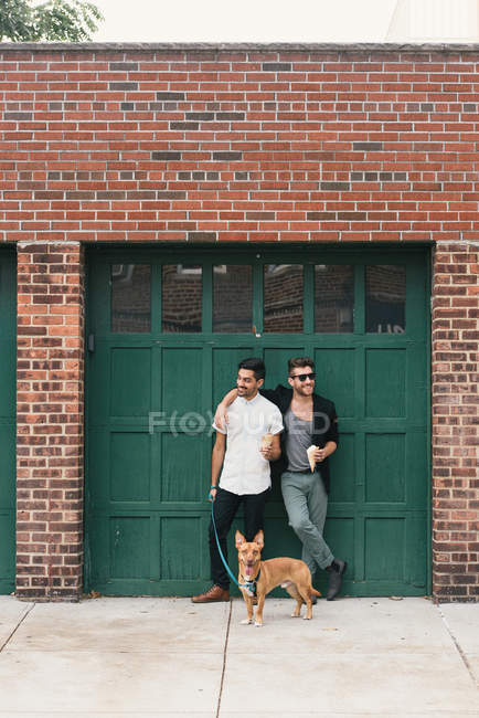 Young male couple with dog leaning on garage, eating ice cream cones — Stock Photo