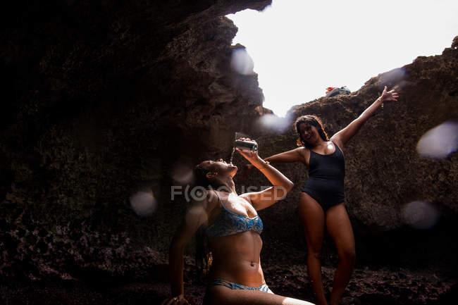 Amigos en cueva vistiendo trajes de baño y posando, Oahu, Hawaii, EE.UU. - foto de stock