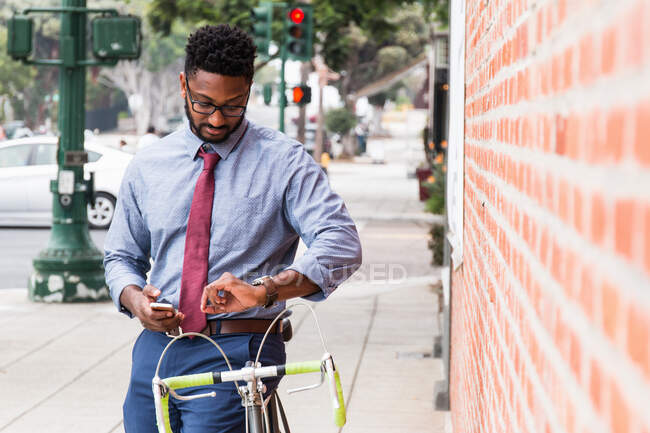 Young man standing beside bicycle, using smartphone, looking at wristwatch — Stock Photo
