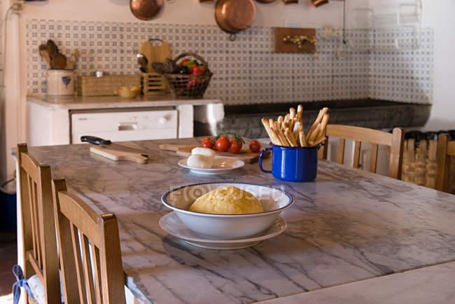 Ingredeints, tabla de cortar y cuchillo en la mesa de la cocina - foto de stock