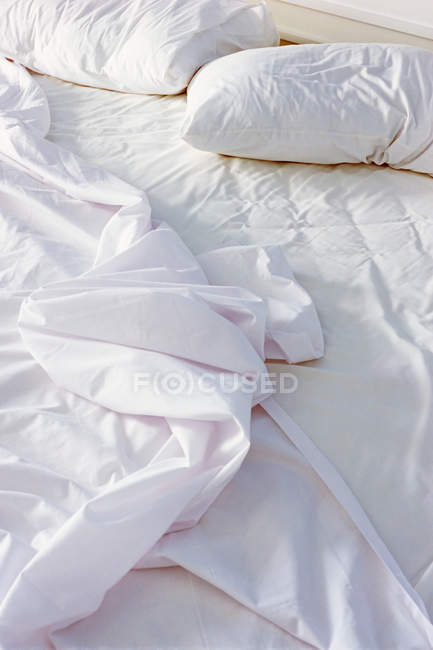 Hojas arrugadas en cama en el dormitorio - foto de stock