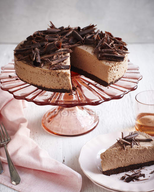 Shocolate cheesecake sur rose cakestand et tranche sur assiette — Photo de stock