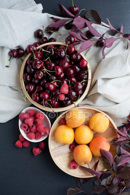Still life of fresh fruits in bowls and tablecloth — Stock Photo