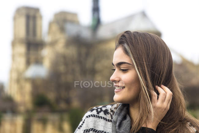 Side view of young woman, Notre Dame Cathedral in background, Paris, France — Stock Photo