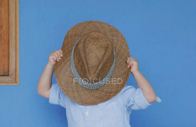 Boy covering face with sun hat — Stock Photo
