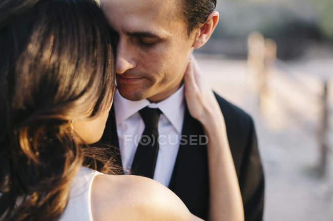 Наречений і наречена обіймають на відкритому повітрі — стокове фото