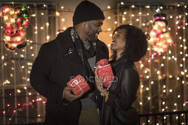 Romantiche coppie felici che godono città durante le vacanze invernali che tiene i regali davanti all'Holiday lights — Foto stock
