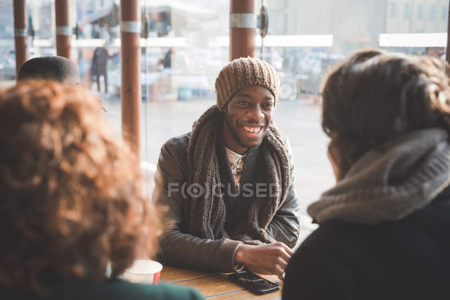 Four young adult friends chatting at sidewalk cafe — Stock Photo