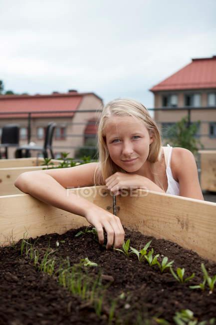 Teenage girl planting seedlings — Stock Photo