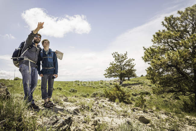 Père et fils adolescent de randonnée avec carte pointant sur paysage, Cody, Wyoming, Usa — Photo de stock