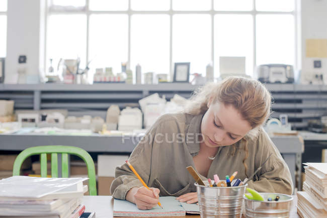 Female print designer working on sketchbook in workshop — Stock Photo