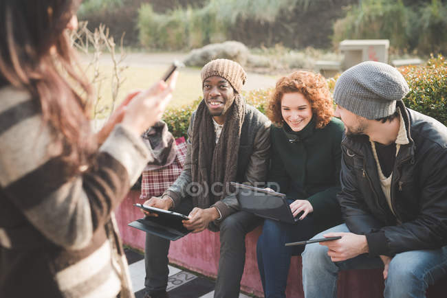 Four young adult friends using smartphones and digital tablets in park — Stock Photo