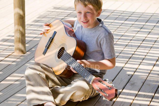 Хлопчик грає гітару на пристані — стокове фото