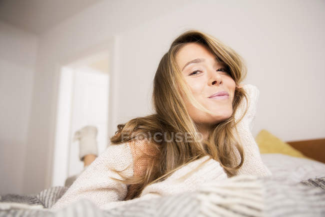 Portrait of beautiful woman lying on bed — Stock Photo