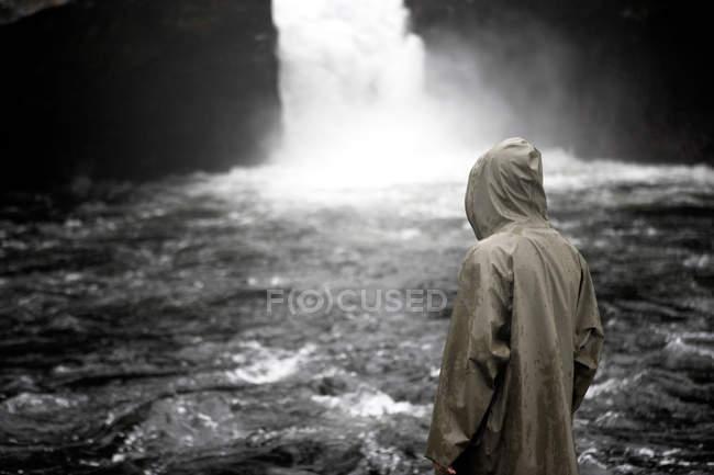 Заднього вигляду людина з можна домислити обличчя стоїть біля водоспаду — стокове фото