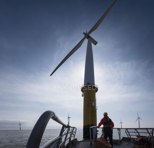 Ingegnere che si prepara a salire la turbina eolica in un parco eolico offshore — Foto stock