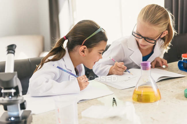 Girls doing science experiments, writing in notebooks — Stock Photo