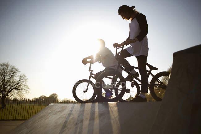 Two young men on bmx bikes at skatepark — Stock Photo