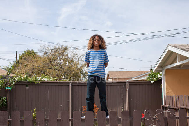 African american Boy standing on fence — Stock Photo