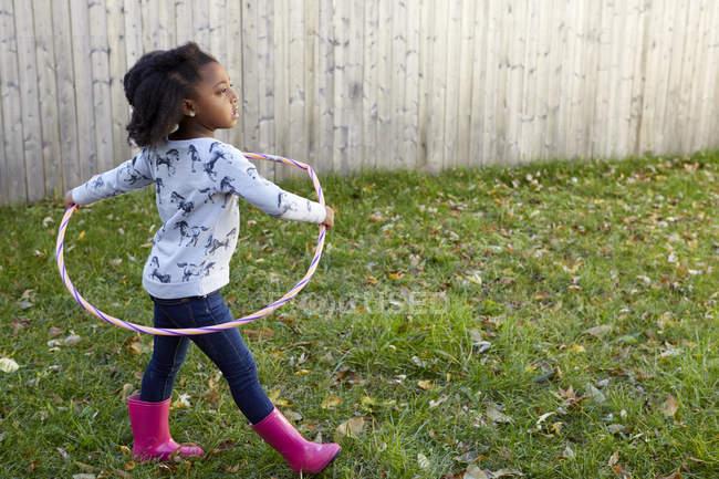 Симпатичні дівчата грають в саду з пластмасовою Хооп — стокове фото
