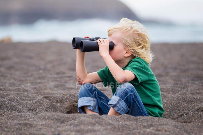Boy using binoculars on beach — Stock Photo